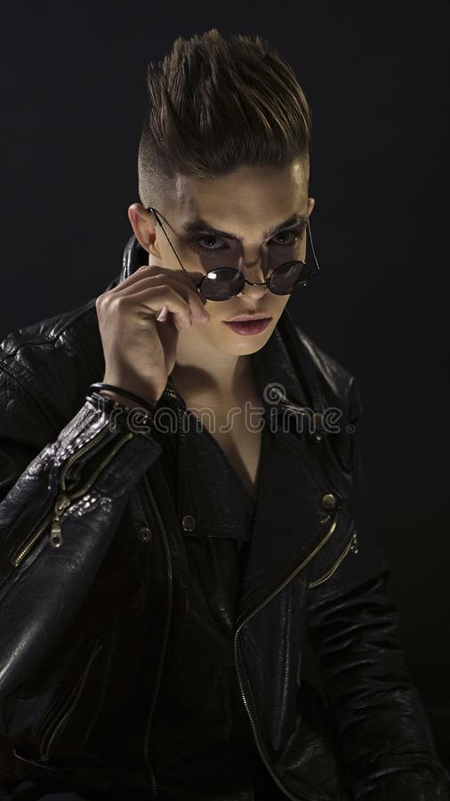 Młodego człowieka portret z round okularami przeciwsłonecznymi Elegancka przystojna seksowna chłopiec w czarny rzemiennej modnej  zdjęcia stock