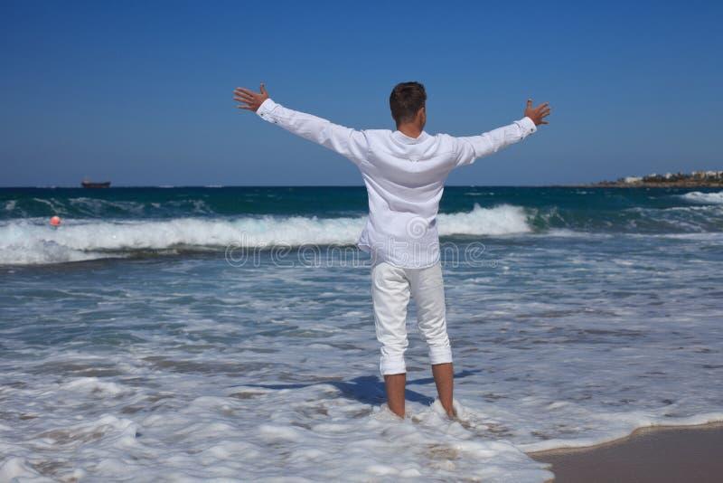 Młodego człowieka pozyci ręki szeroko rozpościerać przy seashore zdjęcie royalty free