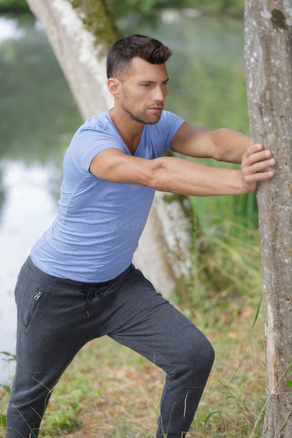Młodego człowieka rozciągania noga po ciężkiego treningu obraz stock
