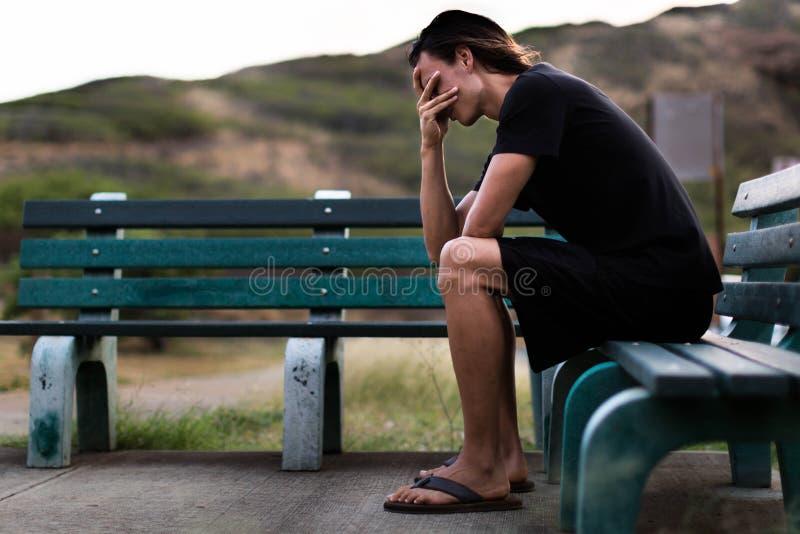 Młodego człowieka siedzący puszek deprymujący z jego rękami nad twarzą obraz stock