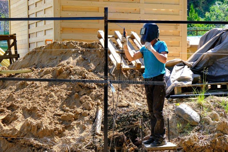 Młodego człowieka spawacz przy pracą Spawalnicza maska na twarzy spawki metalu łuku spawie na budowie, błękitne iskry lata strony zdjęcie royalty free