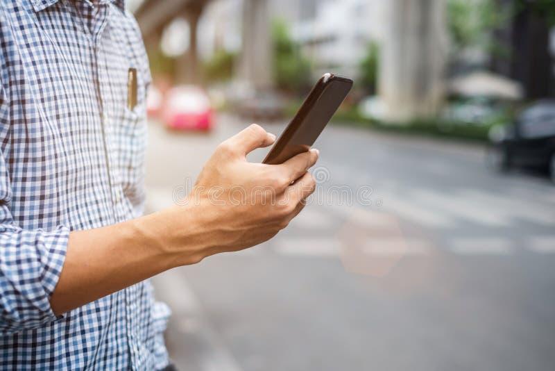 Młodego człowieka turysta lub przypadkowego biznesmena rozkazuje taxi przez taksówki zastosowania na smartphone w miasto ulicie,  obrazy stock