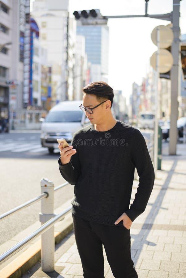 Młodego człowieka use smartphone na drodze dla informaci w Japonia zdjęcia royalty free