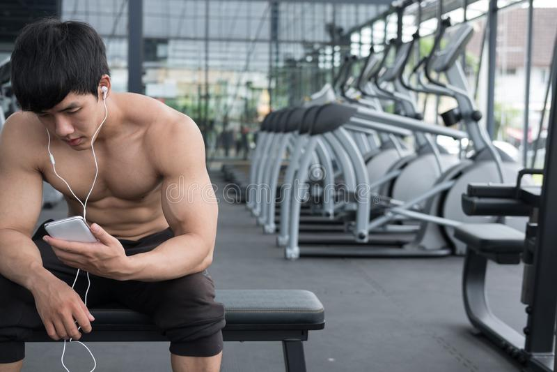 młodego człowieka use telefon komórkowy w sprawności fizycznej centrum męski atlety liste zdjęcie royalty free
