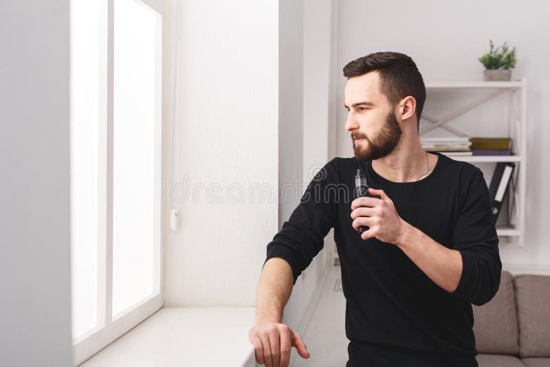 Młodego człowieka vaping papieros przy okno w domu zdjęcie royalty free