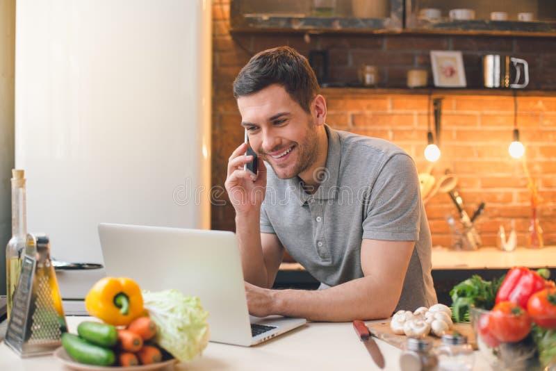 Młodego Człowieka weganinu posiłku przygotowanie Używać laptop zdjęcie royalty free