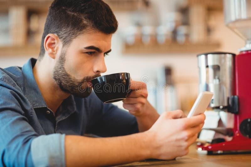 Młodego człowieka wysylanie sms na telefonie komórkowym podczas gdy mieć kawę zdjęcia stock