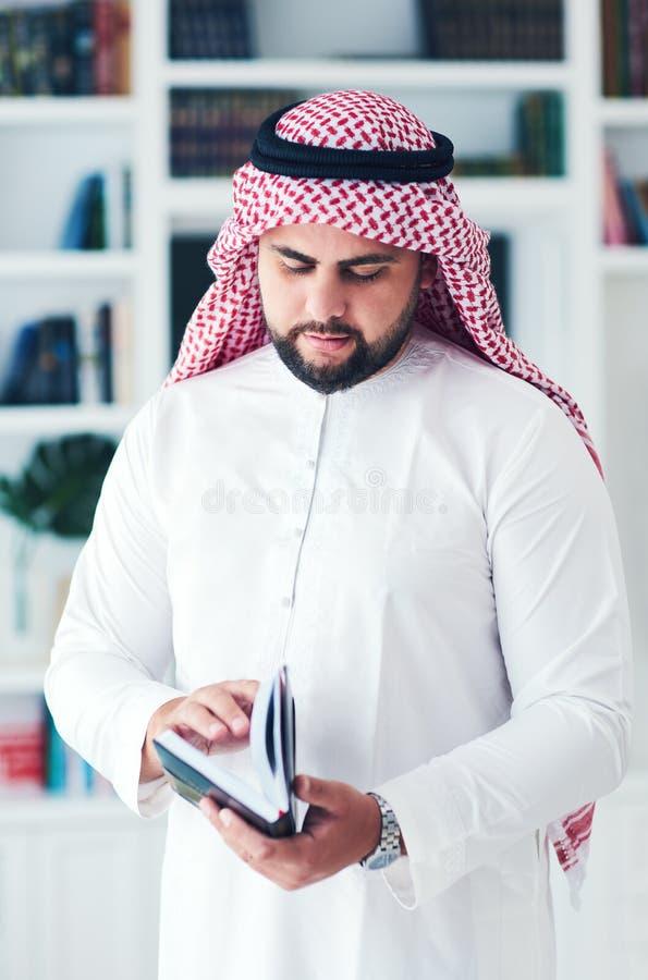 Młodego dorosłego muzułmańskiego mężczyzny czytelnicza książka indoors obraz stock