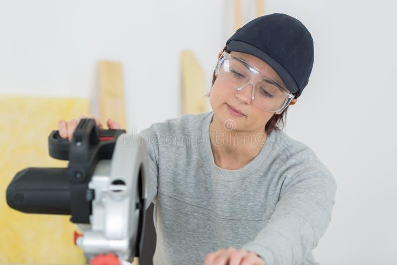 Młodego dorosłej kobiety woodworker tnąca deska w warsztacie obrazy stock