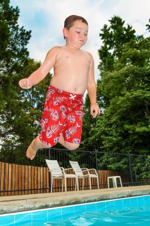 Młodego dziecka doskakiwanie w basen zdjęcie royalty free