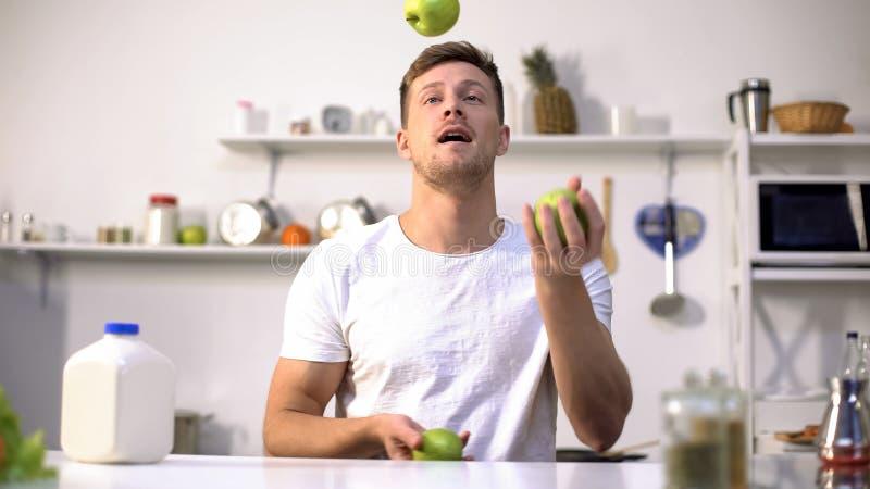 Młodego faceta kuglarscy zieleni jabłka, zaczynać dietę i zdrowego styl życia, witaminy zdjęcie stock