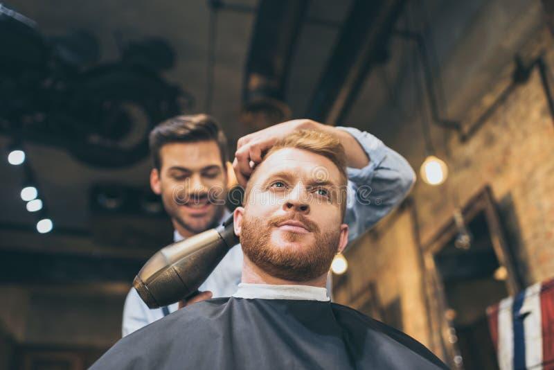 Młodego fryzjera męskiego suszarniczy włosy klient z włosianą suszarką obraz royalty free