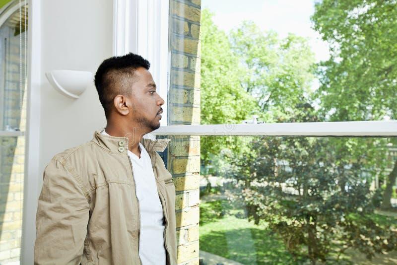 Młodego Indiańskiego mężczyzna przyglądający okno out fotografia royalty free