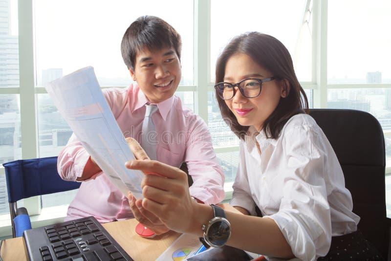 Młodego mężczyzna i kobiety spotkanie w biurowej pracującego stołu scenie dla obraz stock