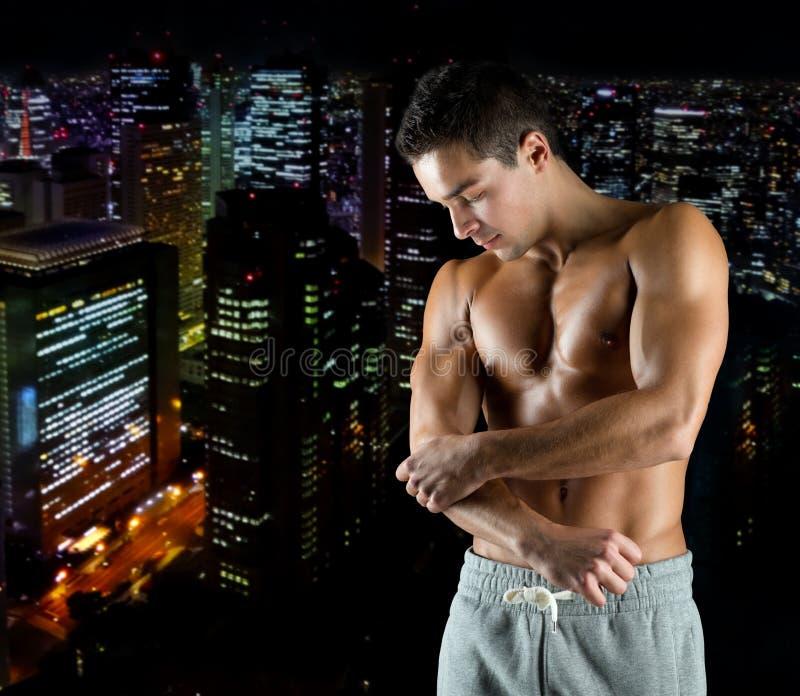 Młodego męskiego bodybuilder zdradzony wzruszający łokieć fotografia stock