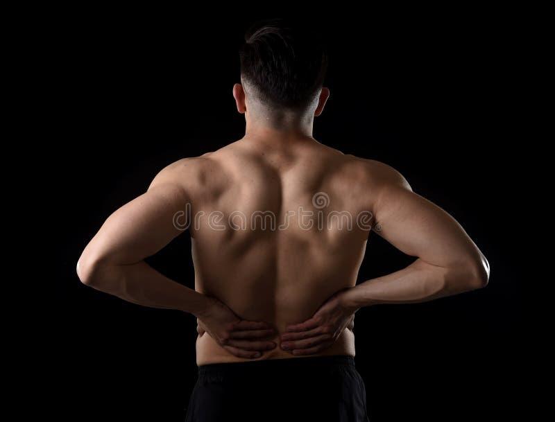 Młodego mięśniowego ciała sporta mężczyzna mienia depresji plecy bolesna talia z jego wręcza cierpienie ból zdjęcia royalty free