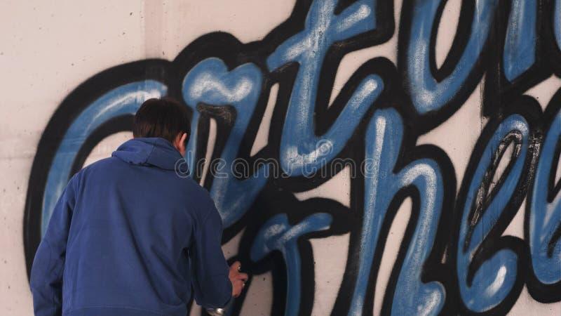 Młodego miastowego malarza graffiti rysunkowi listy na ścianie obrazy royalty free