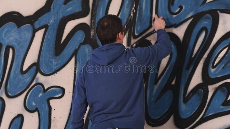 Młodego miastowego malarza rysunkowi graffiti na ścianie fotografia stock