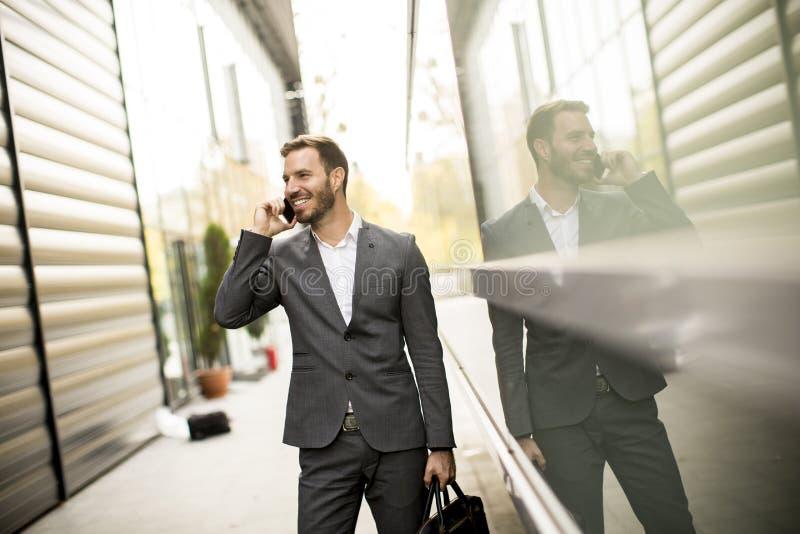 Młodego pomyślnego mężczyzna wykonawczy biznesmen używa jego wiszącą ozdobę cel zdjęcia stock