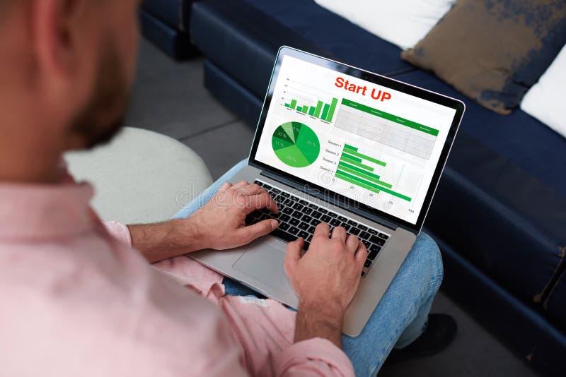 Młodego przedsiębiorcy ruchliwie działanie z statystyki dane i analizować występ pisać na maszynie na notatniku obrazy royalty free