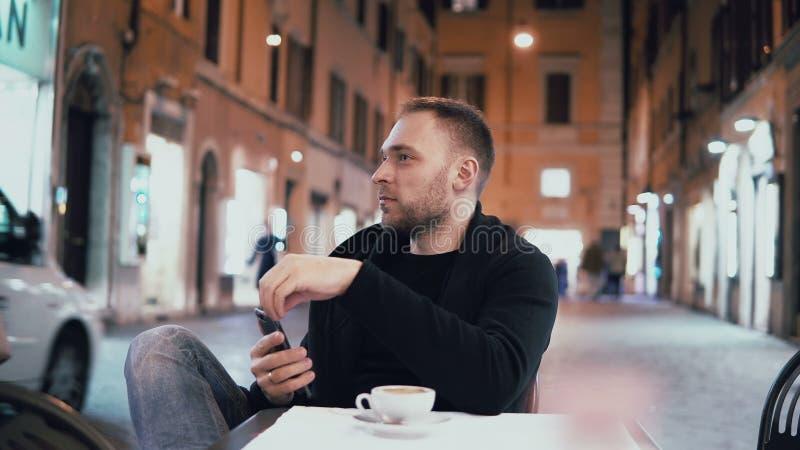 Młodego przystojnego mężczyzna siedzący outside w miasta mienia i kawiarni smartphone Samiec pije kawę w wieczór fotografia stock