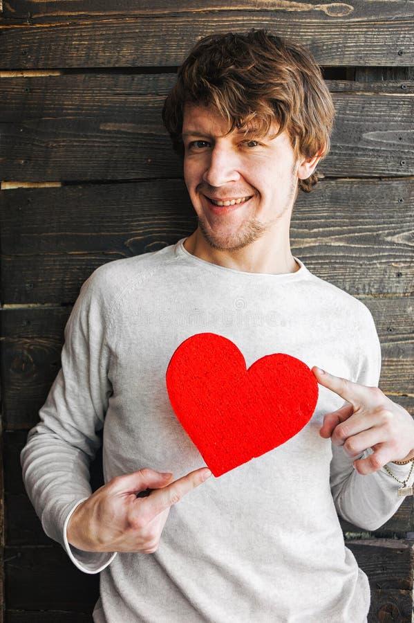 Młodego rozochoconego uśmiechniętego mężczyzna mienia serca czerwony znak obrazy royalty free