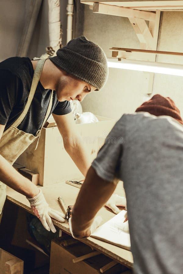 Młodego rzemieślnika pomaga kolega z nakreśleniem fotografia royalty free