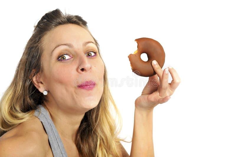 Młodego seksownego niegrzecznego kobiety łasowania czekoladowego pączka szczęśliwy winny dla niezdrowego odżywiania zdjęcia royalty free