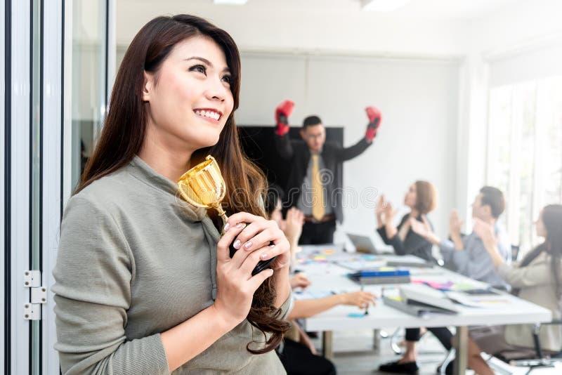Młodego szczęścia ufny azjatykci bizneswoman i drużyna wygrywa złocistego trofeum w biurze Pomyślna biznes drużyna nagradz zdjęcia stock