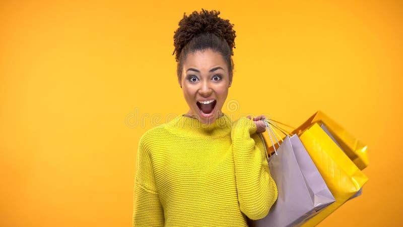 Młodego szczęśliwego żeńskiego mienia kolorowe torby na zakupy, sprzedaży niespodzianka, konsumeryzm zdjęcia royalty free