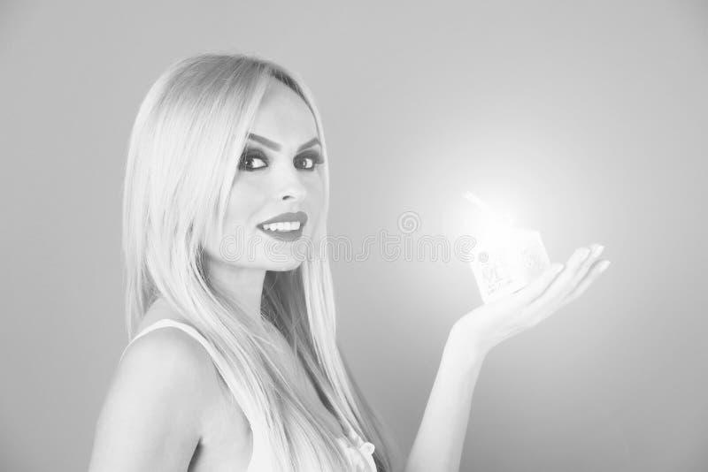 Młodego uwodzicielskiego blondynki kobiety chwyta prezenta mały biały pudełko fotografia stock