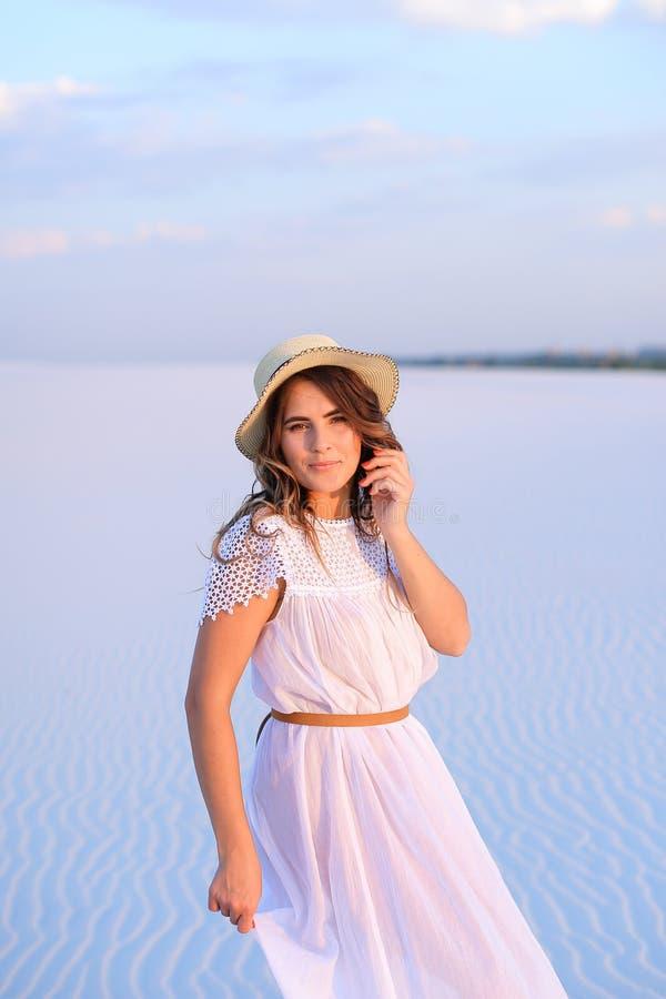 Młodej ładnej kobiety chodzący bareffot na piasku, weaaring biali dresy zdjęcie stock