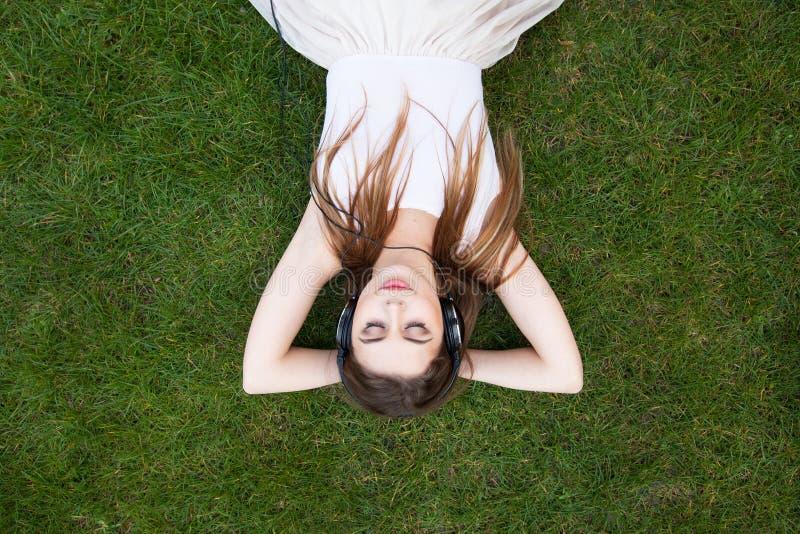 Młodej ładnej kobiety słuchająca muzyka w hełmofonach fotografia stock