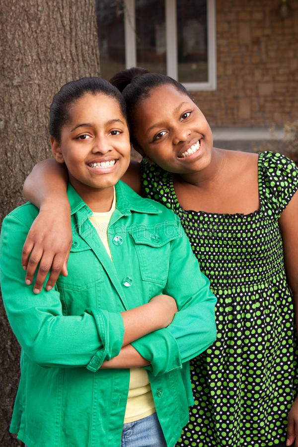 Młodej amerykanin afrykańskiego pochodzenia nastoletniej dziewczyny trwanie outside i ono uśmiecha się zdjęcia stock