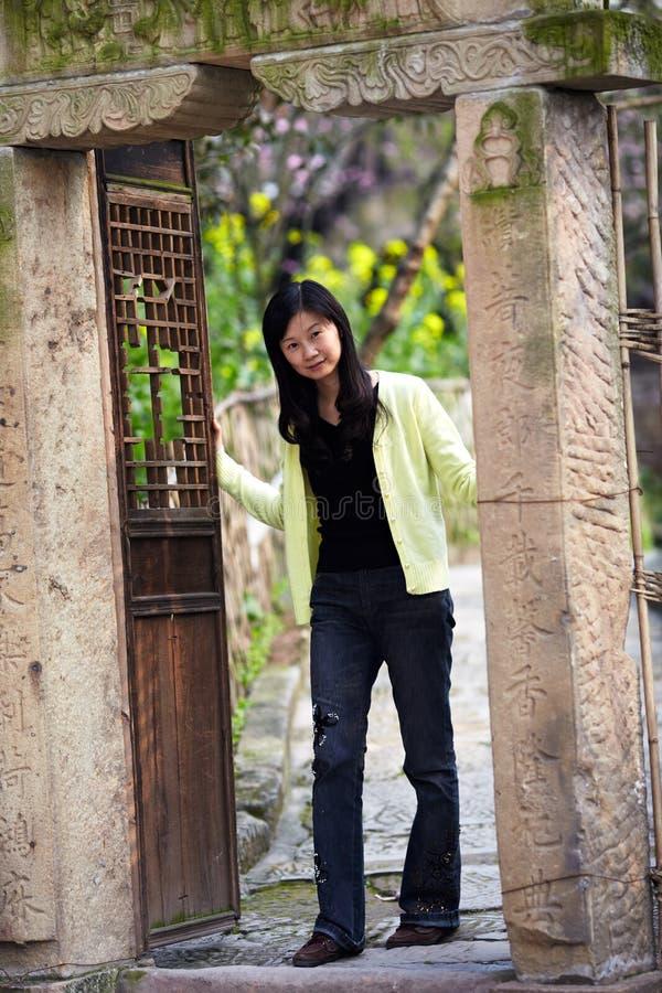 Młodej Asia damy otwarty stary drzwi zdjęcie royalty free