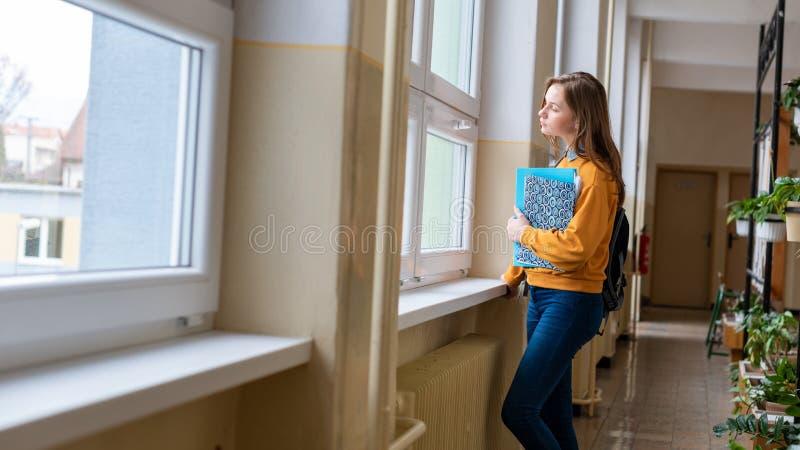 Młodej atrakcyjnej żeńskiej szkoły średniej studencka pozycja okno w korytarzu przy jej szkołą samotnie fotografia stock