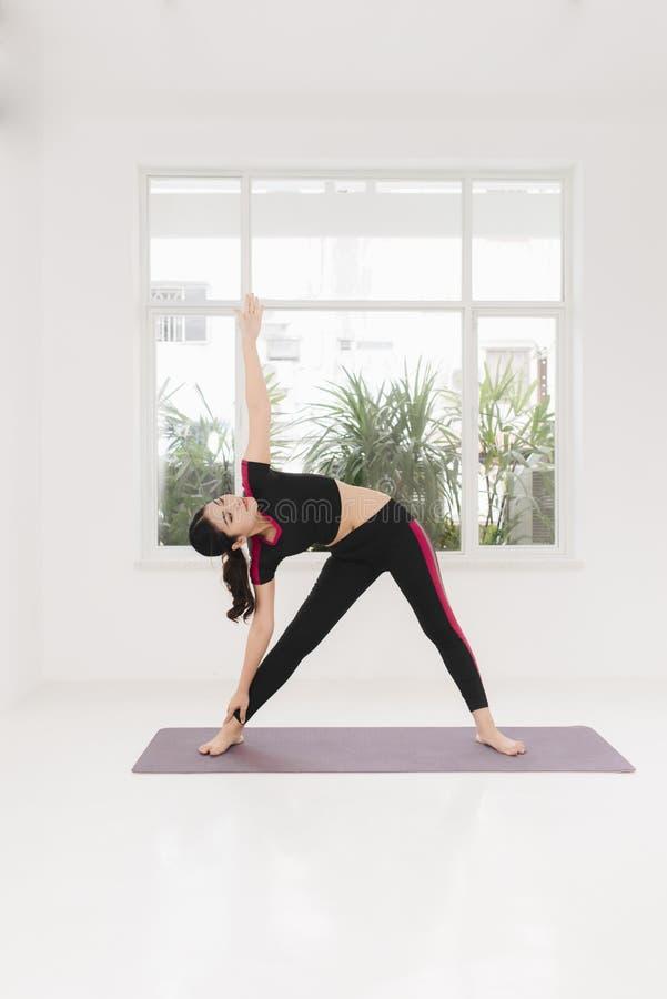 Młodej atrakcyjnej kobiety ćwiczy joga, stojący w wojowniku dwa ćwiczy, będący ubranym sportswear blisko okno, salowa pełna długo obrazy stock