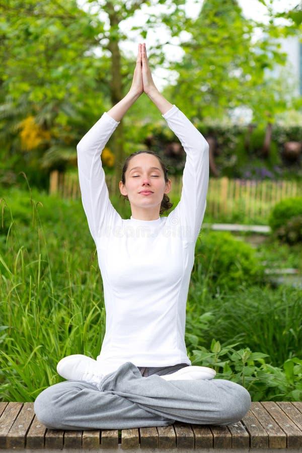 Młodej atrakcyjnej kobiety ćwiczy joga w parku obraz stock