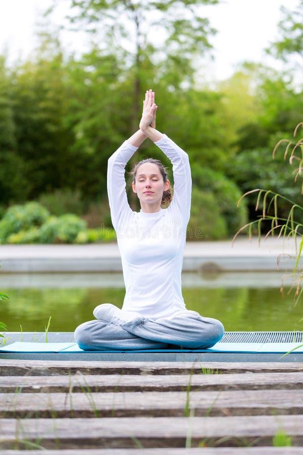 Młodej atrakcyjnej kobiety ćwiczy joga w parku obraz royalty free