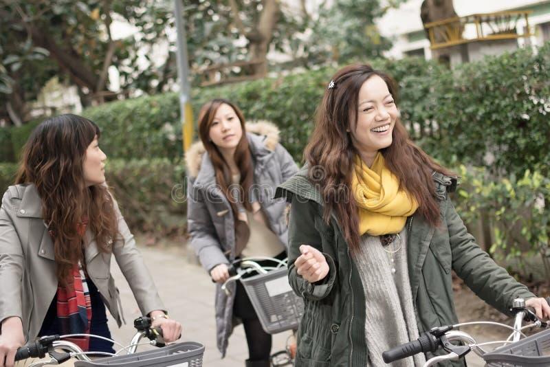 Młodej Azjatyckiej kobiety jeździecki bicykl z przyjaciółmi fotografia stock