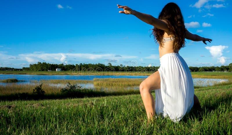 Młodej brunetki hiszpańska kobieta robi wojownika 2 joga pozie w polu obok jeziora z długim kędzierzawym włosy zdjęcia royalty free