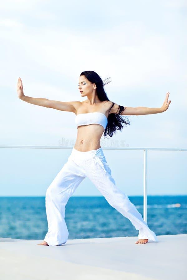 Młodej brunetki kobiety ćwiczy joga morzem zdjęcie stock