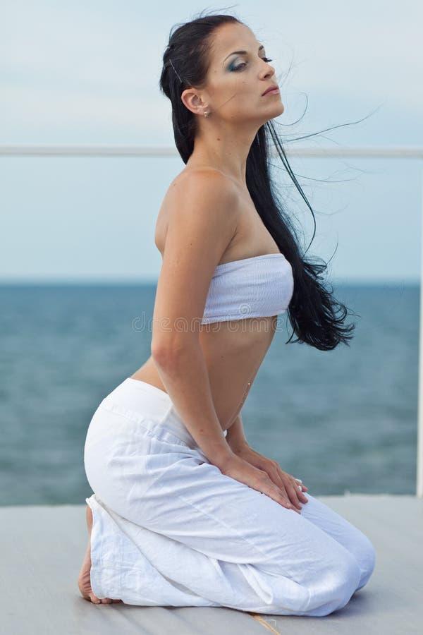 Młodej brunetki kobiety ćwiczy joga morzem obraz stock