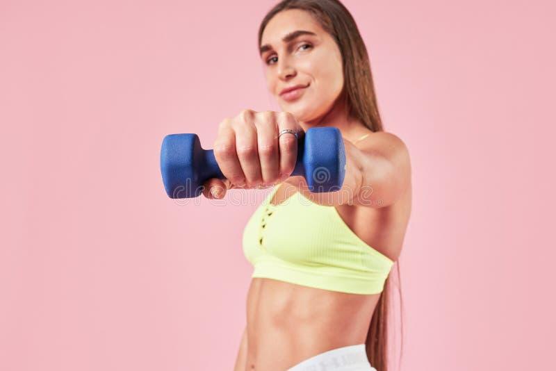 Młodej brunetki kobiety uśmiechnięty sporty szkolenie z dumm dzwonem w ręce, sporta strój na różowym tle fotografia stock