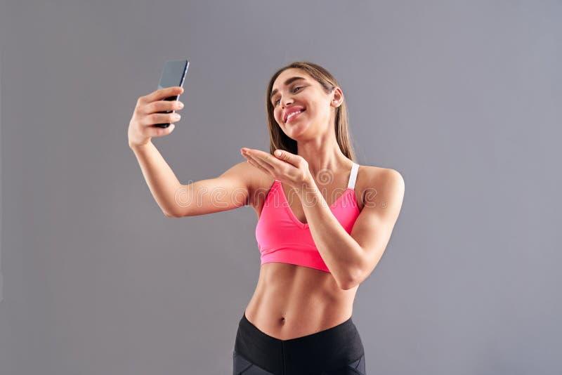 Młodej brunetki uśmiechnięta sporty kobieta robi selfie i przedstawień bicepsom na popielatym tle, pracowniany krótkopęd obraz royalty free