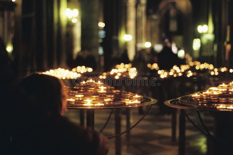 Młodej chłopiec oświetleniowe świeczki w kościół zdjęcia stock
