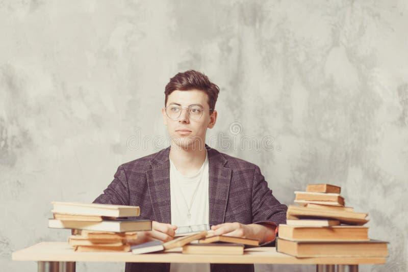 Młodej chłopiec studencki obsiadanie blisko stołu z książkami w szkłach szczęśliwy facet chce uczenie, edukację edukacja w sieci  obraz royalty free