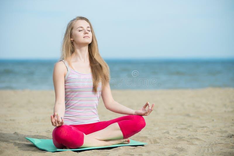 Młodej damy ćwiczy joga Trening blisko oceanu dennego wybrzeża zdjęcia royalty free