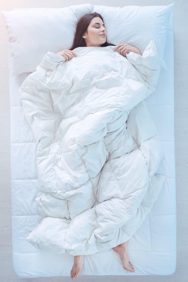 Młodej damy dosypianie w łóżku z duvet obrazy stock