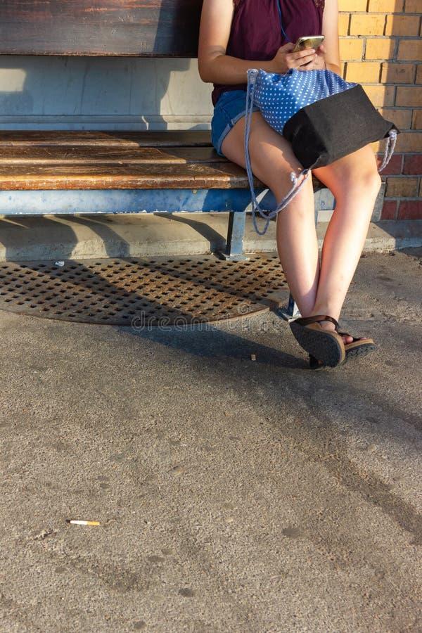 młodej damy obsiadanie na ławce przy Trainstation zdjęcia royalty free